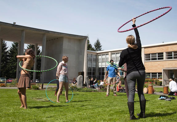 Students hula hoop in campus courtyard
