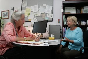 Dr. Leanna Standish and Sharon Hanson talk at a desk.