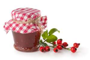 Rose hip jelly with a sprig of rose hips.